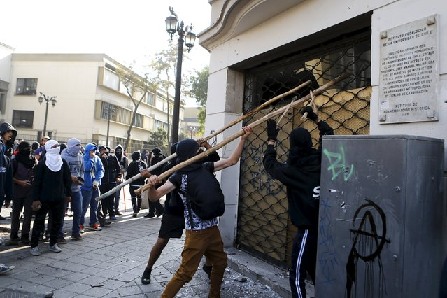 Protesters hit a drugstore during a demonstration to demand changes in the education system at Santiago, May 14, 2015. (Photo by Ivan Alvarado/Reuters)