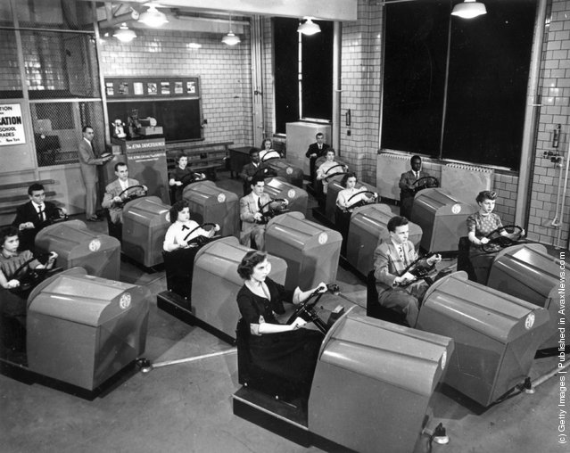 1953: Students at Brooklyn High School in New York learn to handle the controls of a car and experience simulated traffic conditions flashed onto a screen by means of projected film, using the Aetna Drivotrainer