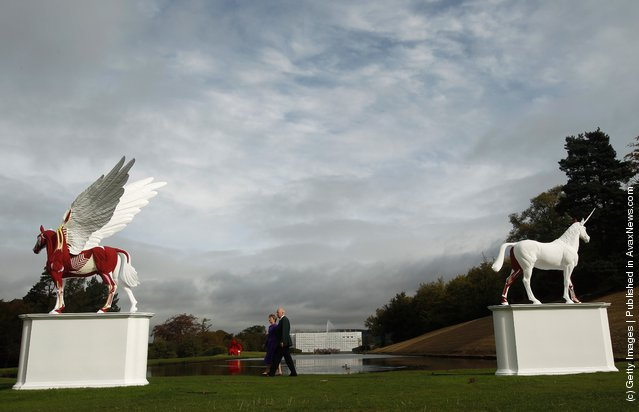 The Duke and Duchess of Devonshire view the sculptures Legend (L) and Myth by Damien Hirst in the gardens of their home Chatsworth House