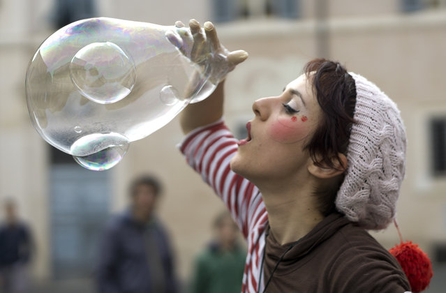 Street performer Zabo makes clustered soap bubbles in downtown Rome, Sunday, April 19, 2015. The bigger bubble is filled with two small ones. (Photo by Domenico Stinellis/AP Photo)