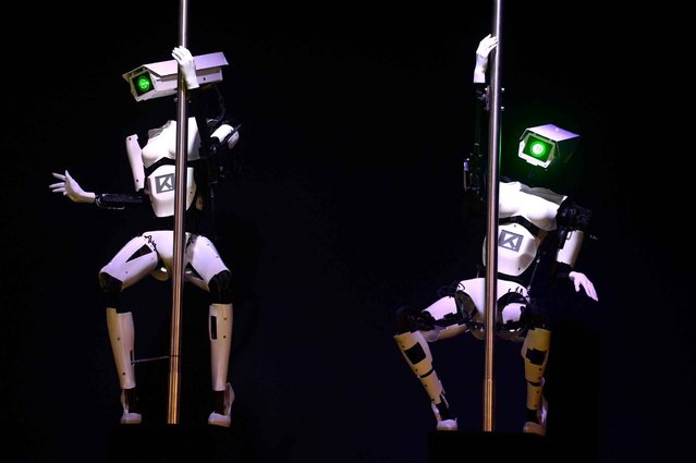 Robots perform a pole dance at the booth of the Tobit Software company on the eve of the start of the 2014 CeBIT technology trade fair on March 9, 2014 in Hannover, central Germany. (Photo by John MacDougall/AFP Photo)