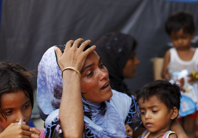 Rahana Begom, a Rohingya migrant who arrived in Indonesia by boat, cries while holding her child inside a temporary shelter, as they wait for medical treatment, in Kuala Langsa in Indonesia's Aceh Province May 16, 2015. (Photo by Reuters/Beawiharta)