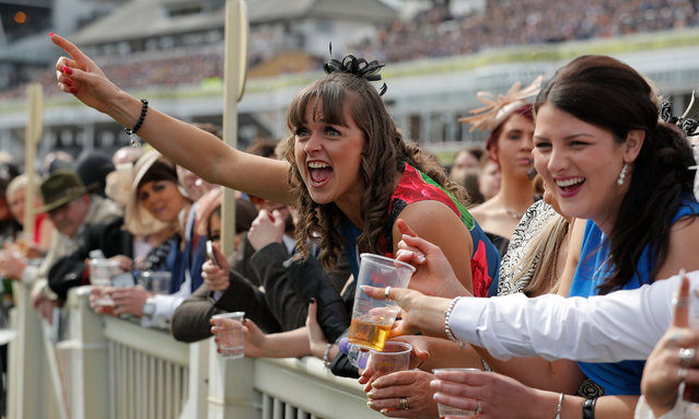 Racegoers cheer as they watch the racing on Ladies Day of the Crabbie's Grand National Festival at Aintree Racecourse on April 8, 2016 in Liverpool, England. (Photo by Tom Jenkins/The Guardian)