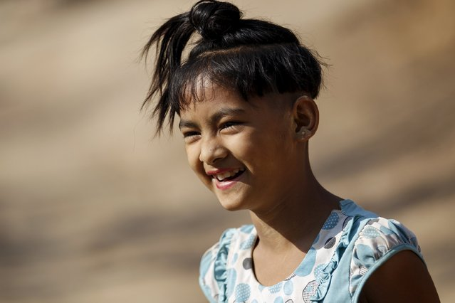 That Mon Kaw, a nine-year-old girl, sports an ancient hairstyle known as Sanyitwine while smiling at Sat Sat Yo village in Nyaung Oo township, near Myanmar's ancient city Bagan April 17, 2015. (Photo by Soe Zeya Tun/Reuters)