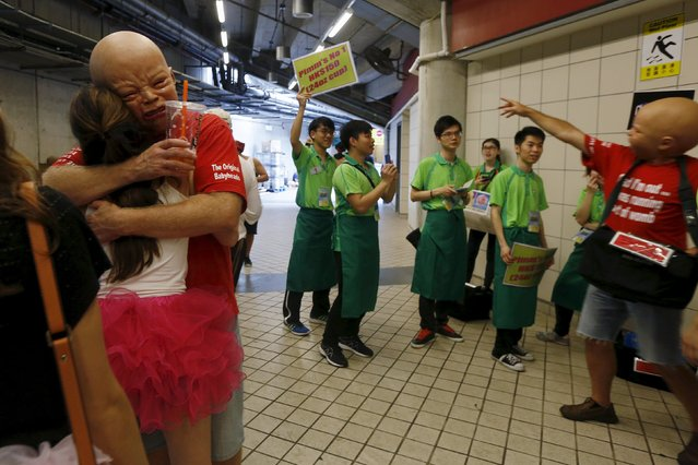 Rugby Union, Hong Kong Sevens, Hong Kong Stadium on April 9, 2016: A fan wearing a mask is hugged. (Photo by Bobby Yip/Reuters)