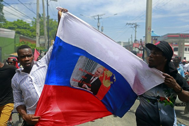 "Anti-government demonstrators hold a Russian flag with a picture of Russian President Vladimir Putin that reads in Creole ""Long live Putin. Down with Donald Trump"" in Port-au-Prince, Haiti, Sunday, June 9, 2019. Protesters denouncing corruption paralyzed much of the capital as they demanded the removal of President Jovenel Moise. (Photo by Dieu Nalio Chery/AP Photo)"