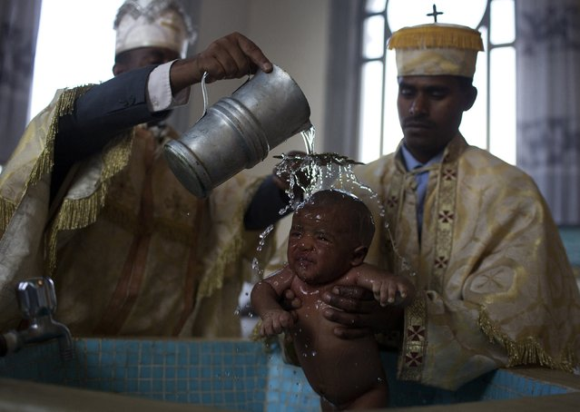 Christian Orthodox priests baptise a baby in the Medhane Alem Cathedral in Addis Ababa, Ethiopia, May 18, 2015. (Photo by Siegfried Modola/Reuters)