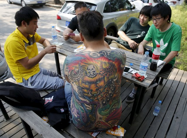 A man, with a tattooed back, plays a poker game with his friends in Beijing, China, May 25, 2015. (Photo by Kim Kyung-Hoon/Reuters)