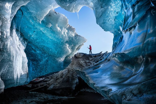 """""""Winter Cave"""". One of the local ice guide guys arriving at a remote ice cave in southeast Iceland. (Photo and caption by Marcelo Castro/National Geographic Traveler Photo Contest)"""