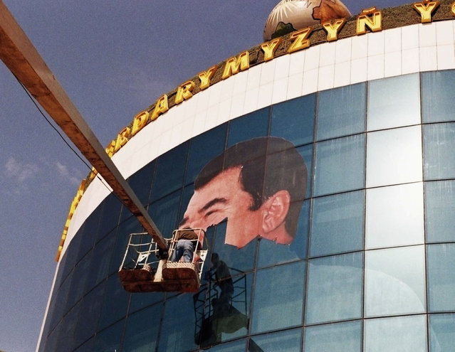 A worker removes a portrait of the late President Saparmurat Niyazov from a building in Ashgabat February, 2006. (Photo by Reuters/Stringer)