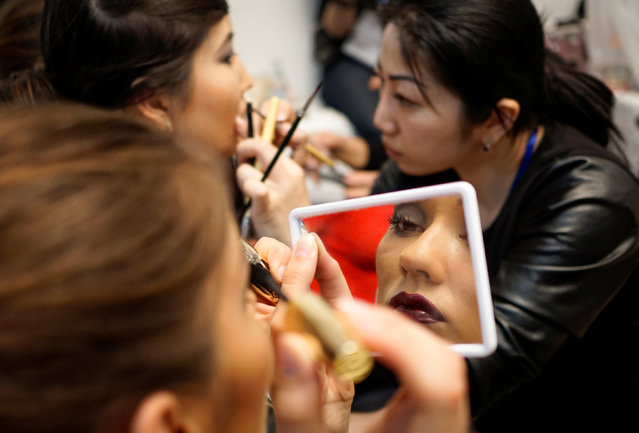 A model is reflected in a mirror as she applies make up backstage during Kazakhstan Fashion Week in Almaty, Kazakhstan, April 19, 2016. (Photo by Shamil Zhumatov/Reuters)