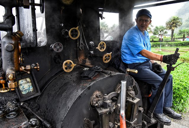 Train driver Hari Chettri sits in the engine of Darjeeling Himalayan Railway steam train, which runs on a 2 foot gauge railway and is a UNESCO World Heritage Site, as it leaves Batasia Loop in Darjeeling, India, June 25, 2019. (Photo by Ranita Roy/Reuters)