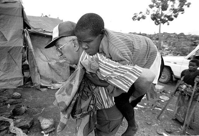 P. Jeau Chaptal from White Fathers carries an ill and exhausted Rwandan refugee to a makeshift clinic in the Mugunga camp as refugees make their way toward Rwanda; 1996. (Photo by Carol Guzy/The Washington Post)
