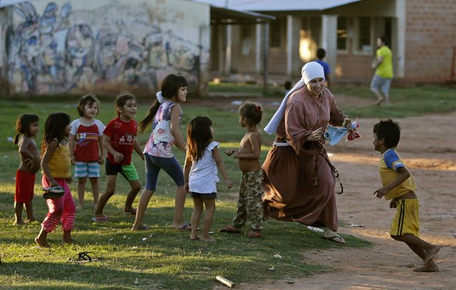 A sister of the Franciscan order plays with children in Lambare city, near Asuncion, April 2, 2014. The poverty rate in Paraguay fell 8.6 percentage points in 2011-2013 to 23.8 percent, the government reported on Wednesday, attributing this to an increase in employment and welfare programs. (Photo by Jorge Adorno/Reuters)