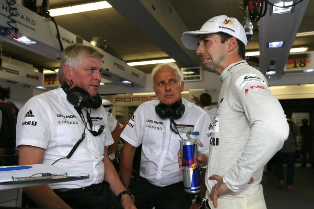 Swiss driver Neel Jani, right, reacts as he talks with team's members during the 83rd 24-hour Le Mans endurance race, in Le Mans, western France, Saturday, June 13, 2015. (AP Photo/David Vincent)