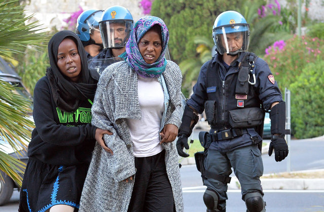 Italian police officers remove migrants in Ventimiglia, at the Italian-French border Tuesday, June 16, 2015. Police at Italy's Mediterranean border with France have forcibly removed some of the African migrants who have been camping out for days in hopes of continuing their journeys farther north. The migrants, mostly from Sudan and Eritrea, have been camped out for five days after French border police refused to let them cross. (Luca Zennaro/ANSA via AP)