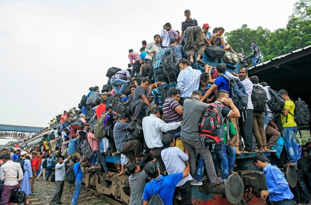 With no seats available inside, around 2,000 men, women and children climb on train roofs or cling on to the sides during busy periods. (Photo by Yousuf Tushar/Solent News & Photo Agency)
