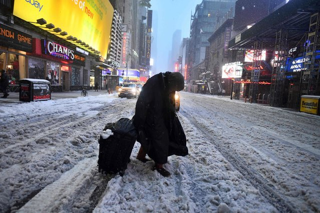 People walk the snow and sleet- covered streets of New York on March 14, 2017. Winter Storm Stella unleashed its fury on much of the northeastern United States on March 14 dropping snow and sleet across the region and leading to school closures and thousands of flight cancellations. Stella, the most powerful winter storm of the season, was forecast to dump up to two feet (60 centimeters) of snow in New York and whip the area with combined with winds of up to 60 miles per hour (95 kilometers per hour), causing treacherous whiteout conditions. (Photo by Jewel Samad/AFP Photo)