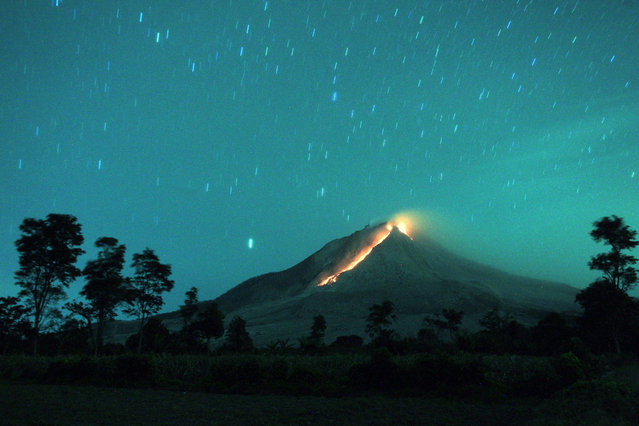 A long exposure picture shows molten lava spilling from the crater of Mount Sinabung as seen from Berastepu village in Karo, North Sumatra province, Indonesia, 24 June 2015. Thousands of villagers were evacuated following the weekend eruption of Mount Sinabung in Indonesia's North Sumatra province, with more expected to follow, officials said on 16 June. Mount Sinabung has erupted intermittently since late 2013. (Photo by Dedi Sahputra/EPA)