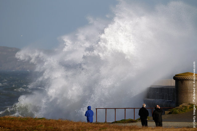 People watch waves crash over the Holyhead breakwater as the search continues for the crew of cargo vessel The Swanland which sank off north Wales on November 27, 2011 in Holyhead, Wales