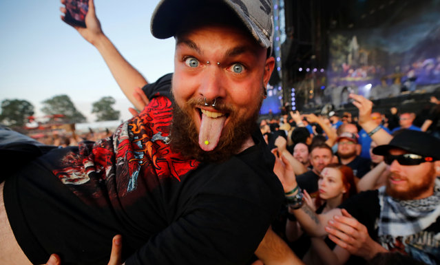 """A heavy metal fan sticks out his tongue as he surfs on top of the crowd during the performance of the German power metal band """"Powerwolf"""" at the world's largest heavy metal festival, the Wacken Open Air 2019, in Wacken, Germany on August 3, 2019. (Photo by Wolfgang Rattay/Reuters)"""