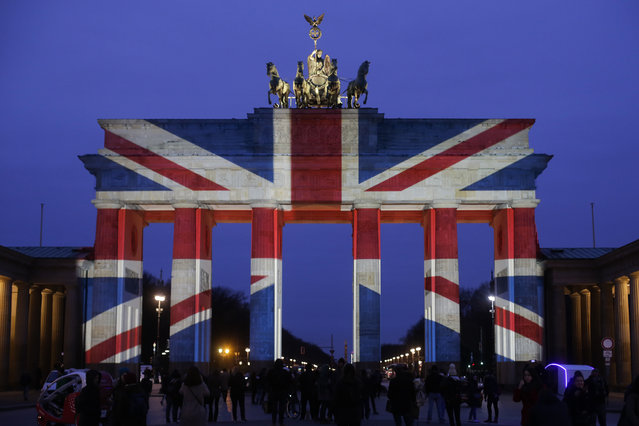 The Brandenburg Gate is illuminated in the colors of  the British national flag to pay tribute to the victims of an attack in London, at the German capital in Berlin, Thursday, March 23, 2017. (Photo by Markus Schreiber/AP Photo)