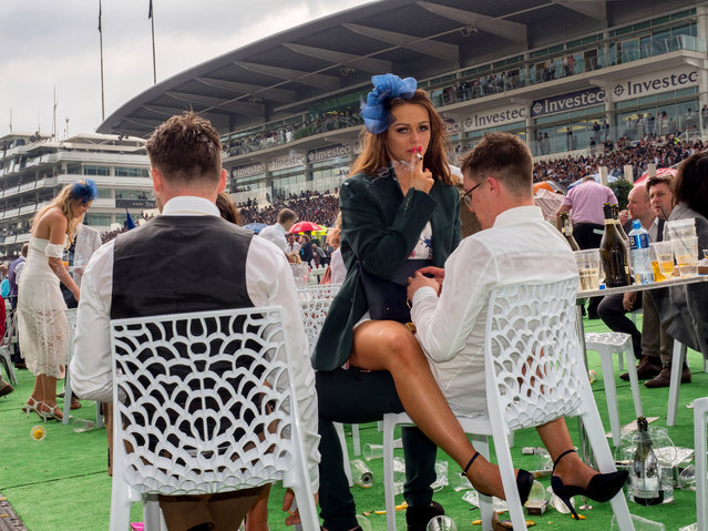 A young woman smokes a cigarette straddled across a man's lap on Ladies' Day at Epsom, England on June 2, 2017. Ladies' Day is traditionally held on the first Friday of June, a multitude of ladies and gents head to Epsom Downs Racecourse to experience a day full of high octane racing, music, glamour and fashion. (Photo by Peter Dench/Getty Images Reportage)