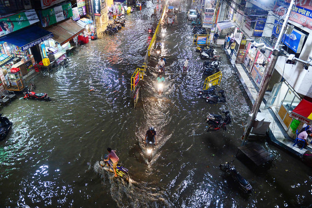 Commuters make their way through a flooded street after heavy rains in Allahabad, India on August 13, 2019. (Photo by Sanjay Kanojia/AFP Photo)