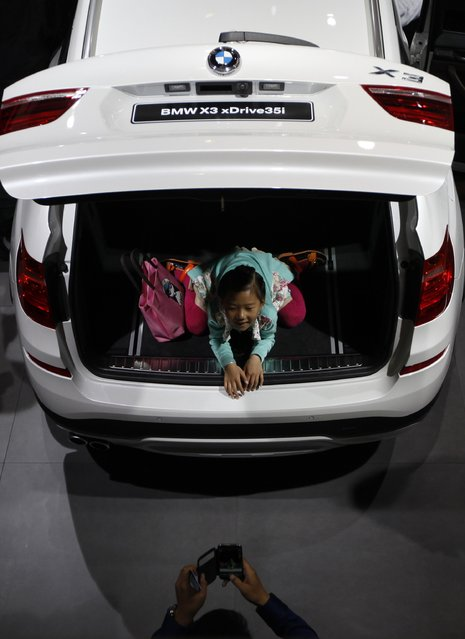 """A girl poses for a photo in a BMW X3 car on display at the China International Exhibition Center new venue during the """"Auto China 2014"""" Beijing International Automotive Exhibition in Beijing on April 21, 2014. (Photo by AFP Photo)"""