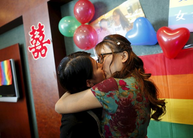 Li Tingting (L) and Teresa kiss at their wedding reception in Beijing, China July 2, 2015. (Photo by Kim Kyung-Hoon/Reuters)