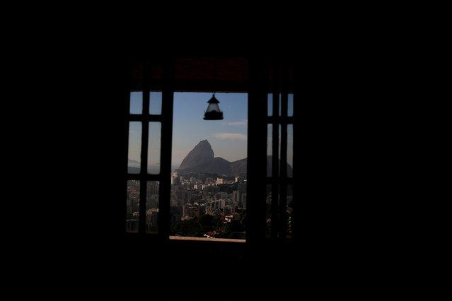 Sugar Loaf mountain is seen through a window of Favelinha (Little favela) hostel in Pereira da Silva favela, in Rio de Janeiro, Brazil, April 21, 2016. (Photo by Pilar Olivares/Reuters)