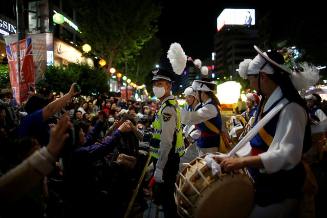 A traditional band performs in front of crowd as a policemen (C) stands guard during a lotus lantern parade in celebration of the upcoming birthday of Buddha in Seoul, South Korea, May 7, 2016. (Photo by Kim Hong-Ji/Reuters)
