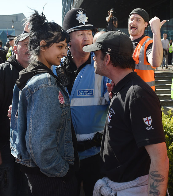 """An angry English Defence League member clashes in Birmingham with a calm member of the public in an image widely shared on social media yesterday, April 9, 2017. Around 50 EDL protestors turned up for a rally; a local mosque had opted to counter the far-right group's antagonism with a """"best of British"""" tea party which was attented by over 300 people. (Photo by Joe Giddens/PA Wire)"""