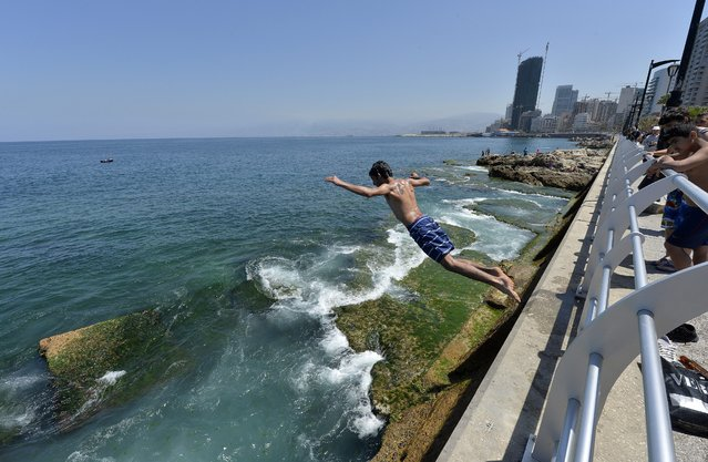 A youth jumps into the Mediterranean sea while others watch him at Manara's seaside in Beirut, Lebanon, 27 April 2014. Lebanese are going to the beach to cool off as summer weather begins in the region. (Photo by Wael Hamzeh/EPA)