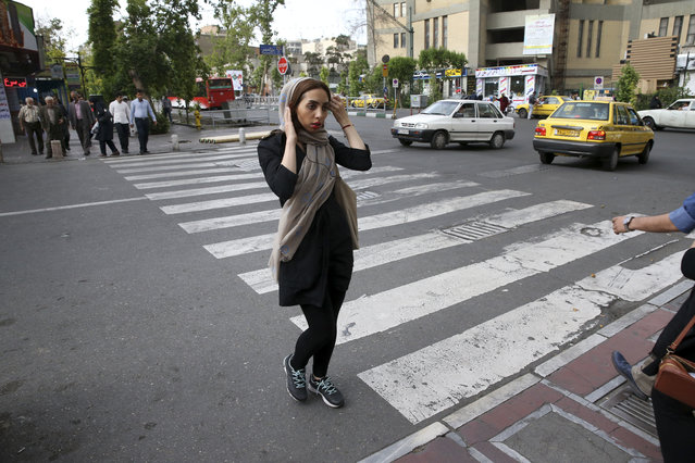An Iranian woman adjusts her head scarf while crossing a street in downtown Tehran, Iran, Tuesday, April 26, 2016. Tehran police chief Gen. Hossein Sajedinia recently announced his department had deployed 7,000 male and female officers for a new plainclothes division – the largest such undercover assignment in memory. Critics fear the unit's main focus will be enforcing the government-mandated Islamic dress code, which requires women be modestly covered from head to toe. (Photo by Vahid Salemi/AP Photo)