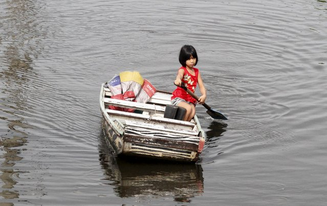 A girl paddles a makeshift boat in Artex Compound, the lowest point in the city, which is prone to flooding during monsoon seasons, in Malabon, Metro Manila in the Philippines July 11, 2015. The United Nations Population Fund, (UNFPA) called on humanitarian agencies to redouble efforts in addressing the special needs of vulnerable populations in preparedness and response measures to disasters as nations observe World Population Day on July 11, a statement said. (Photo by Lorgina Minguito/Reuters)