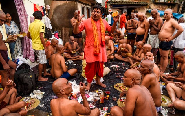 "A priest assists Hindu devotees as they perform ""Tarpan"", a ritual to pay obedience to one's forefathers on the last day for offering prayers to ancestors called ""Pitrupaksh"", in Mumbai on September 28, 2019. In Hindu mythology, this day is also called ""Mahalaya"" and described as the day when the gods created the ten-armed goddess Durga to destroy the demon king Mahishasura who plotted to drive out the gods from their kingdom. (Photo by Indranil Mukherjee/AFP Photo)"