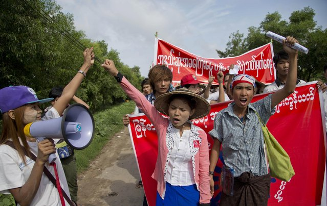 Myanmar factory workers shout slogans during a march against proposed minimum wage at Hlaing Thar Yar industrial zone, suburb of Yangon, Myanmar, Sunday, July 12, 2015. Several hundred workers in Myanmar staged a peaceful demonstration Sunday to demand that a new daily minimum wage be set higher than proposed. (Photo by Gemunu Amarasinghe/AP Photo)