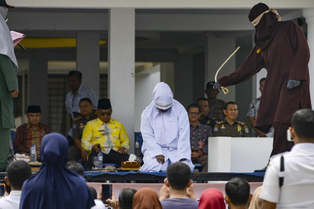 A woman (C, in white) is whipped in public by a member of the Sharia police in Banda Aceh on September 19, 2019. A trio of canoodling couples were publicly flogged in Indonesia's Aceh province on September 19, charged with breaking local Islamic law that outlaws public displays of affection. Despite international condemnation, whipping is a common punishment for a range of offences in the deeply conservative region on Sumatra island, including gambling, drinking alcohol, and having gay or pre-marital s*x. (Photo by Chaideer Mahyuddin/AFP Photo)