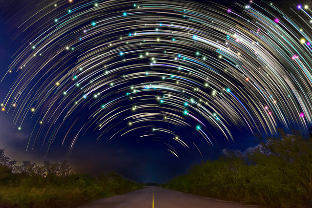 Star trails are pictured from a road in Singapore. These astonishing images of night sky are captured by Singapore based photographer Justin Ng. The pictures were taken between November 2013 to January 2014. It show's star trail caused by the earth's rotation and also can be achieved by zooming the DSLR lens inward or outward in small steps using a dedicated motorized zooming device. (Photo by  Justin Ng/Barcroft Media)