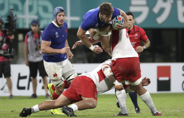 France's Damian Penaud is tackled by Tongan defenders during the Rugby World Cup Pool C game at Kumamoto Stadium between France and Tonga in Kumamoto, Japan, Sunday, October 6, 2019. (Photo by Aaron Favila/AP Photo)