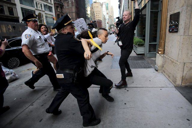 A protester is detained by New York Police Department officers during a rally for Eric Garner who was killed one year ago by police in New York July 17, 2015. Family and supporters on Friday marked the anniversary of the police killing of Garner with rallies and vigils demanding police reforms and justice in the controversial case. (Photo by Eduardo Munoz/Reuters)