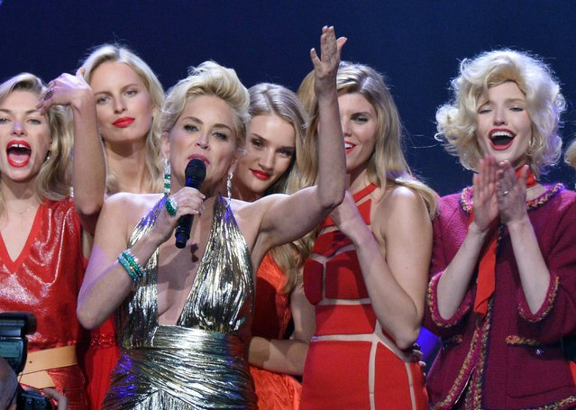 Actress Sharon Stone, front, conducts an auction with, at back from left, Australian model Jessica Hart, Czech model Karolina Kurkova, British model and actress Rosie Huntington-Whiteley, Belarussian model Maryna Linchuk and South Korean model Soo Joo Park during the Foundation for AIDS Research's 21st annual Cinema Against AIDS alongside the Cannes Film Festival in southern France, on May 22, 2014. (Photo by Alberto Pizzoli/AFP Photo)
