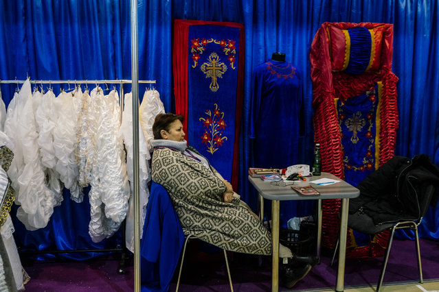 A participant sits at the stand of a coffin manufacturer during a funeral exhibition in Moscow on October 31, 2019. (Photo by Dimitar Dilkoff/AFP Photo)