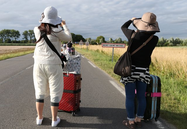 Tourists walk with their luggage near Mont Saint-Michel in northwestern France on July 20, 2015 after their bus was forced to drop them off as protesting farmers blocked roads near the tourist spot. Hundreds of angry French farmers blocked roads across northern France, including access to Mont Saint-Michel, one of the country's top tourist spots, demanding higher milk and meat prices. (Photo by Charly Triballeau/AFP Photo)