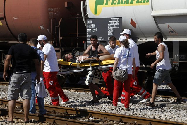 In this photo taken on Thursday, July 23, 2015  Red Cross workers carry to the ambulance a migrant who has been seriously injured after he climbed atop of a tank wagon where he suffered an electric shock, at the railway station in the southern Macedonian town of Gevgelija. (Photo by Boris Grdanoski/AP Photo)