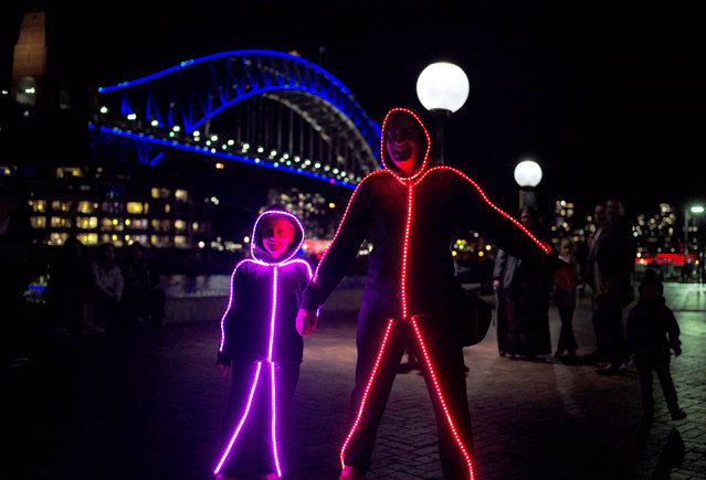 Visitors to the annual Vivid Sydney light festival wear matching illuminated suits alongside the Sydney Harbour Bridge on the second night of the light and sound show in Sydney, Australia, May 28, 2016. (Photo by Jason Reed/Reuters)
