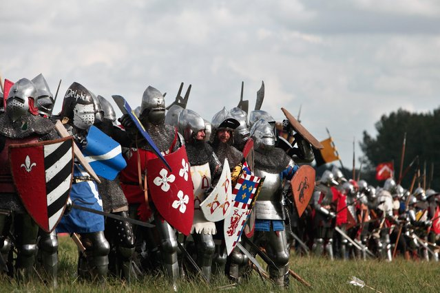 People wear armors as they attend a reenactment of the Battle of Agincourt, in Agincourt, northern France, Saturday, July 25, 2015. (Photo by Thibault Camus/AP Photo)