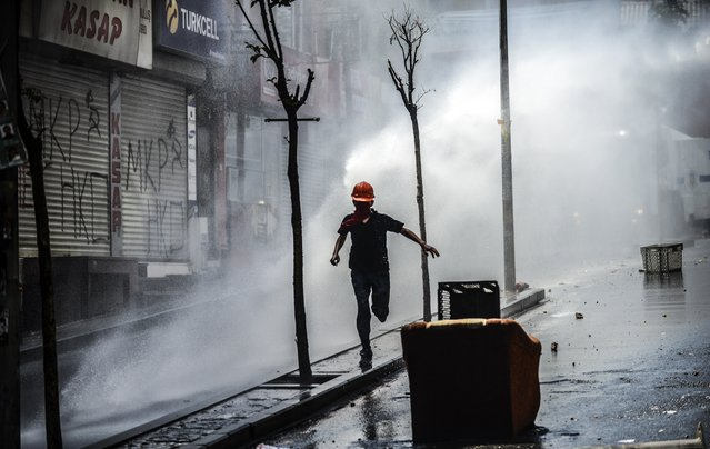 A protester runs away as Turkish riot police use water cannons to disperse protesters during a demonstration against the recent mine accident in Soma, on May 22, 2014, in the Okmeydani district of Istanbul. One man was injured when Turkish riot police today fired tear gas and water cannon to disperse a group of Istanbul protesters hurling Molotov cocktails and stones. (Photo by Bulent Kilic/AFP Photo)