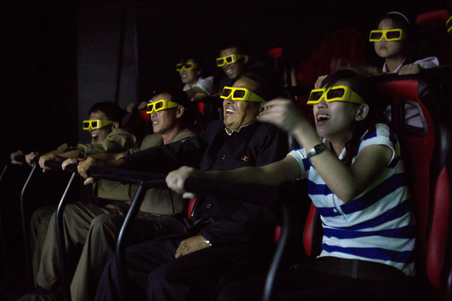 In this September 22, 2013 file photo, North Koreans ride on an amusement park ride while watching a 3D movie at the Rungna People's Pleasure Park in Pyongyang, North Korea. North Korea hates the Hollywood film that revolves around the assassination of its beloved leader, but the country has had a long love affair with cinema – of its own particular styling. (Photo by David Guttenfelder/AP Photo)